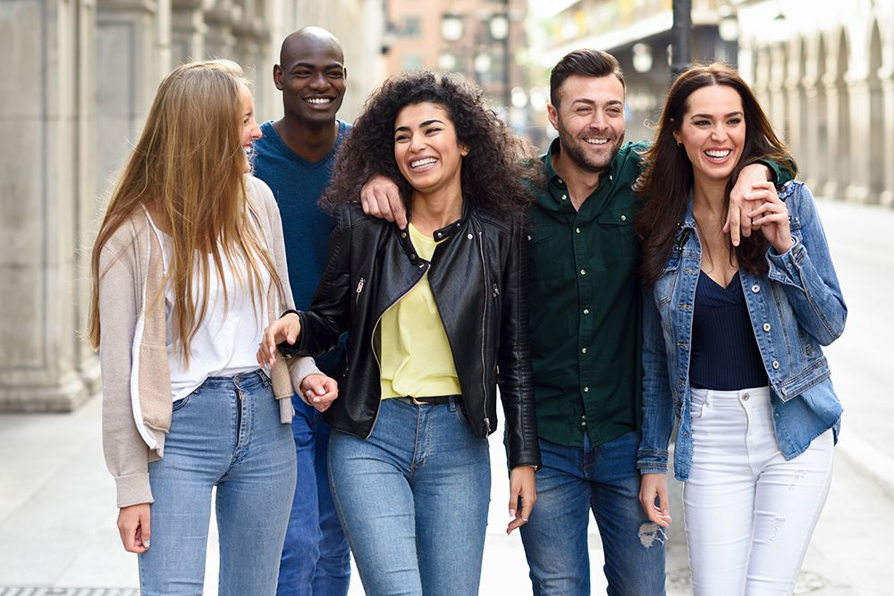 group of adult friends walking in a city while smiling