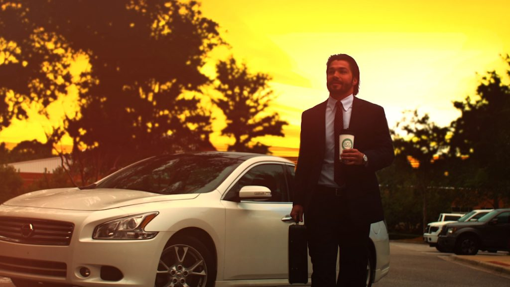 Wealthy man with nice car at sunset