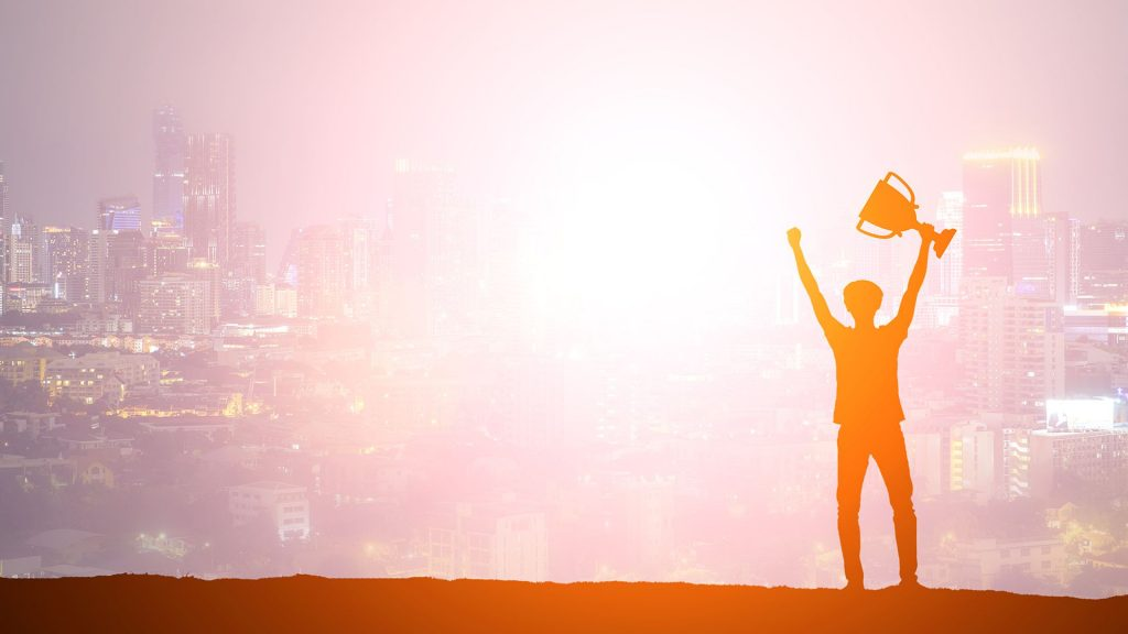Man ins silhouette holding a trophy against a sunset cityscape